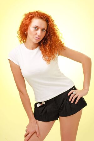 red haired woman: Attractive red haired woman standing on a yellow background Stock Photo