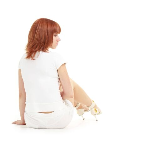 red haired woman: Attractive red haired woman sitting on a white background with copyspace