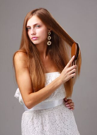 Combing hair. Attractive young lady with comb on a gray background. Stock Photo - 5305597