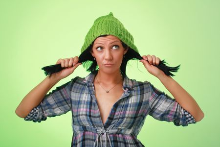 Beautiful girl in green woollen cap on a green background. photo