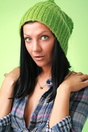 Green eyes. Beautiful girl in green cap on a green background. Stock Photo - 5305616