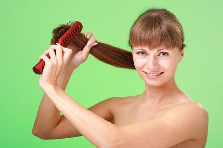 Attractive young lady with comb on a green background. Stock Photo - 5338252