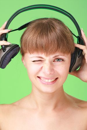 Smiling young lady with headphones on a green background photo