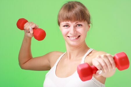Smiling young woman exercising with dumbbells on a green background photo