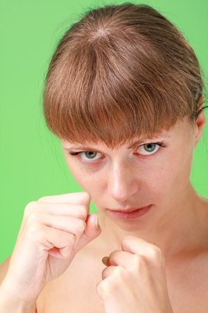 karate. young woman with fists on a green background  photo