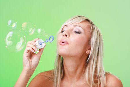 Attractive young lady blowing soap bubbles on a green background photo