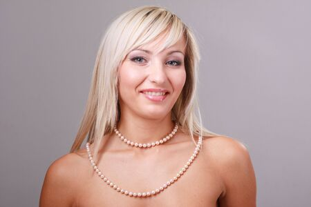 Sexy young woman with pearl necklace on a gray background photo