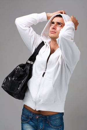 Crisis. Stressed young man on a gray background. Stock Photo - 5579189