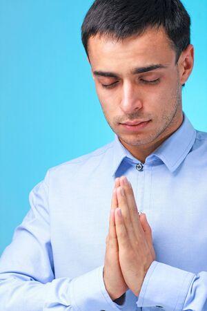 man close up: Namaste. Pregare stretti dell'uomo d'affari su uno sfondo blu.