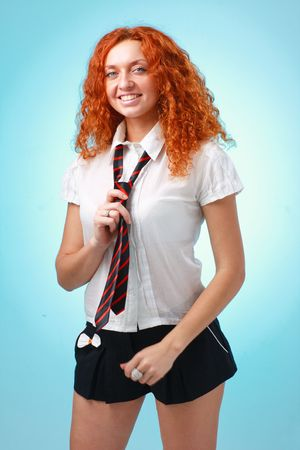 red haired woman: Happy red haired woman standing against blue background Stock Photo