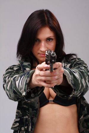 weapons: Attractive young woman with gun on a gray background Stock Photo