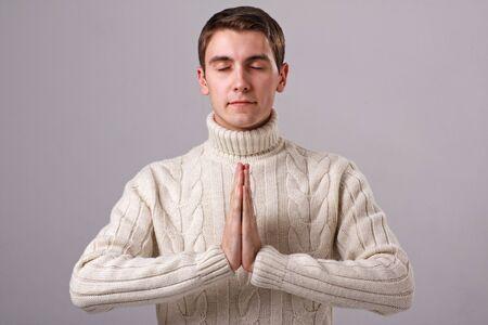 praying man: Namaste. Praying man on a gray background.