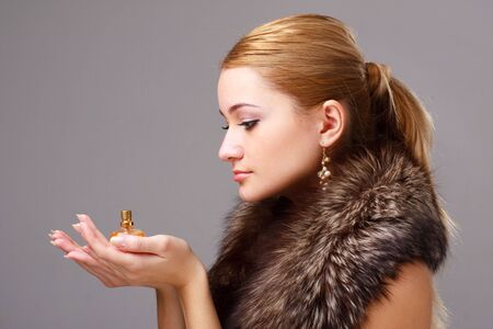 Attractive young woman wearing fur with perfume
