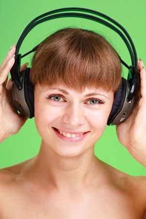 Smiling attractive woman with headphones on a green background photo