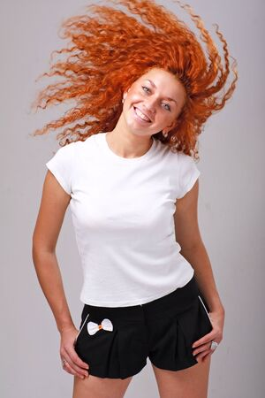 Smiling red haired woman with hair flying on a gray background Stock Photo - 5901664