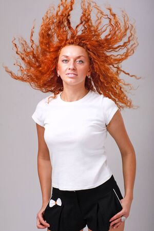 red haired woman: Attractive red haired woman with hair flying, standing on a gray background Stock Photo
