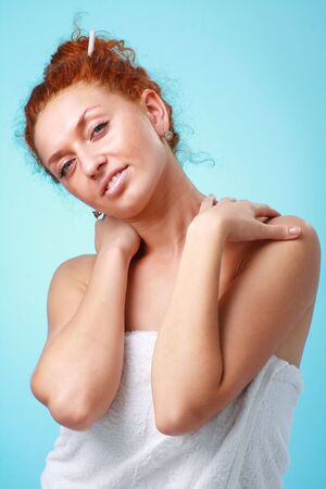 red haired woman: Smiling red haired woman in towel close up on a blue background