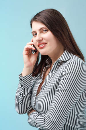 Young woman with mobile phone close up on a blue background photo
