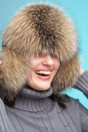 Winter fashion. Smiling woman wearing fur-cap close up. photo