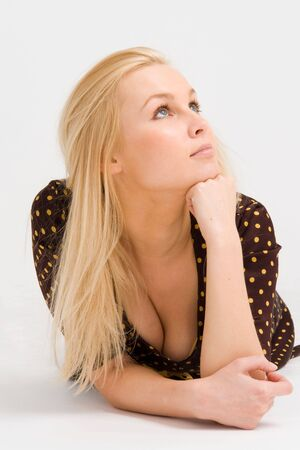 Attractive blond woman lying on a gray background photo