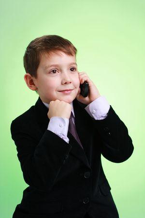 little business man: Poco hombre de negocios con tel�fono m�vil sobre un fondo verde Foto de archivo