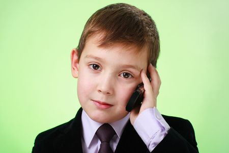 Little business man with cell phone on a green background photo