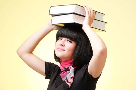 Businesswoman with big books on a yellow background photo