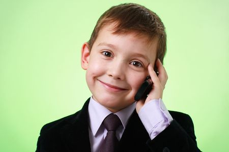 Smiling little business man with cell phone on a green background