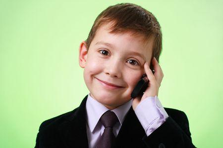 little business man: Sonriente a poco hombre de negocios con tel�fono m�vil sobre un fondo verde