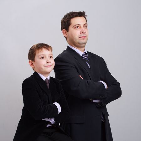 Business family. Father and son in suit on a gray background. photo