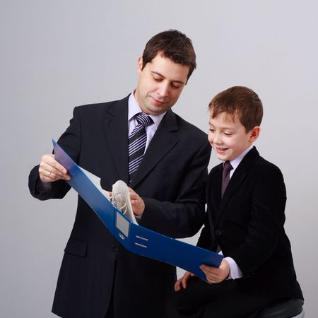 Business training. Father and son on a gray background. photo