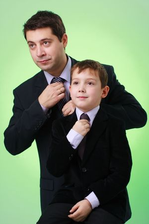 little business man: Business family. Father and son on a green background. Stock Photo