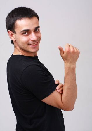 Smiling young man with thumb up on a gray background photo