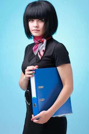 Young business woman with folder on a blue background photo