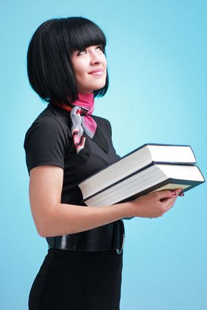 Happy student with big books on a blue background photo