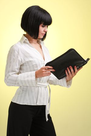 business woman with datebook on a yellow background photo