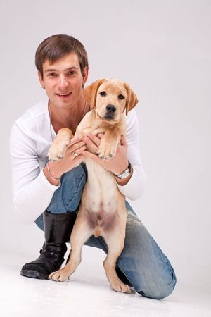 handsome man with Labrador retriever on a gray background.