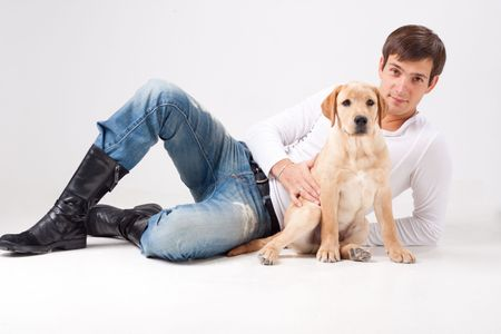 Attractive young man with dog on a gray background. Stock Photo - 6181288