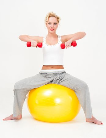 Attractive sportswoman exercising with dumbbells on a big fitness ball photo