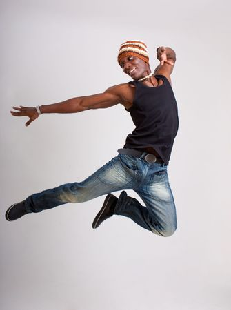 Young dancer jump on a gray background