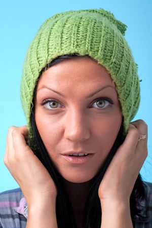 Attractive woman in green woollen cap on a blue background photo