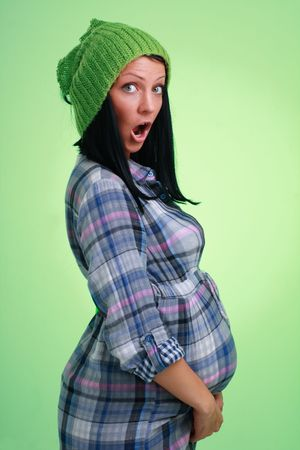 surprised child: Surprised pregnant woman in green woollen cap on a green background. Stock Photo