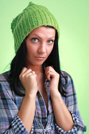Attractive girl in green woollen cap on a green background photo