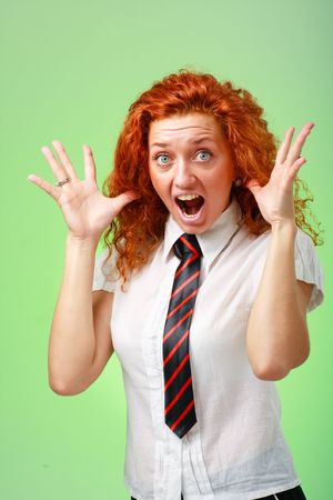 red haired woman: Surprised girl. Beautiful red haired woman on a green background Stock Photo