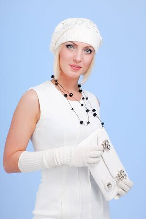 knitwear. young woman wearing a winter cap and gloves on a blue background photo