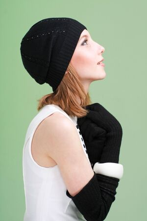 knit cap: knitwear. young woman wearing a winter cap and gloves on a green background