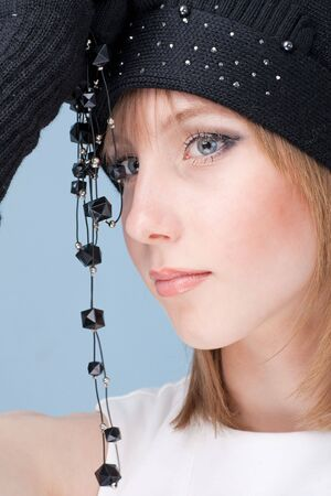 Young woman wearing a winter cap with black necklace closeup photo