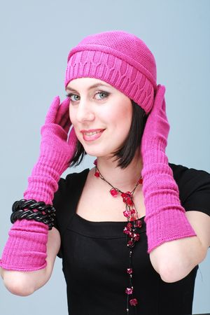 Smiling woman wearing a winter cap and gloves closeup on a blue background. photo