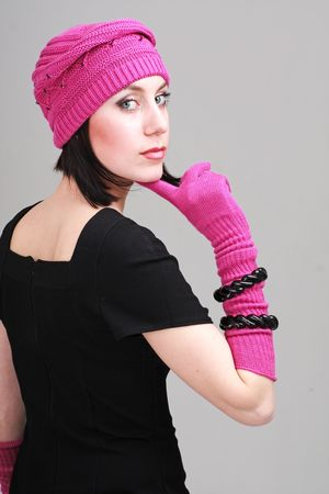 Woman wearing a winter cap and gloves on a gray background. photo