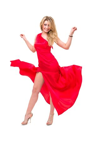 Young woman in red dress dancing against isolated white background photo